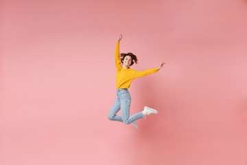 Funny young brunette woman girl in yellow sweater posing isolated on pastel pink background in studio. People lifestyle concept. Mock up copy space. Having fun, fooling around, rising hands, jumping. Wall mural