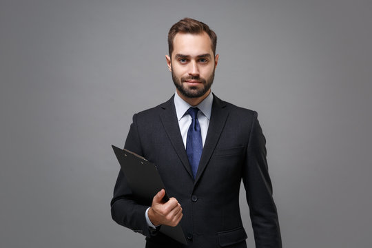 Attractive young business man in classic black suit shirt tie posing isolated on grey background. Achievement career wealth business concept. Mock up copy space. Hold clipboard with papers document.