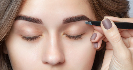 Make-up artist plucks eyebrows with tweezers to a woman. Beautiful thick eyebrows close up.
