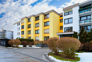 Colorful Modern residential apartment and flat building exterior in Salzburg, of Austria. New luxury house and home complex of yellow color. City Real estate property and condo architecture.