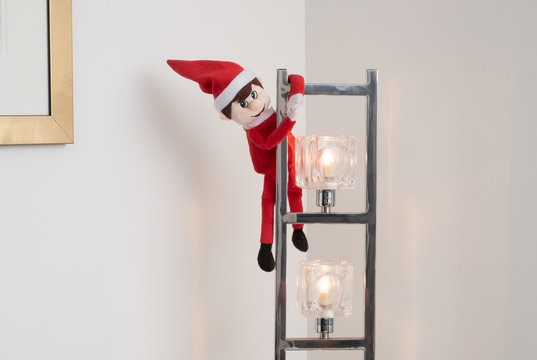 Christmas elf playing tricks hanging off light fitting. Cute tradition of sending Santa's elf to check up on children just before christmas, but elves can be very naughty