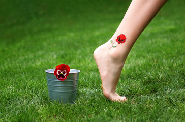 Barefoot female leg with red pansy tattoo walking away from flower in bucket on green grass. Girl foot on nature.