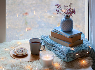 Cozy home. Winter holidays still life. Cup of tea with sweet dessert, candle, books, flowers in blue vase and garland lights at window. Relaxing at cold season at home. Copy space