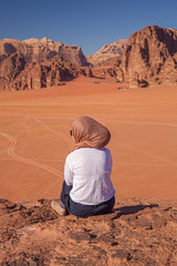 A woman in scarf staring at the desert viewed from behind