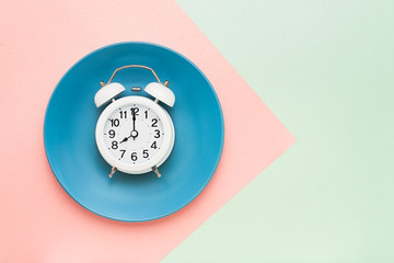 Intermittent fasting concept. White alarm clock on empty blue plate. Top view, copy space.