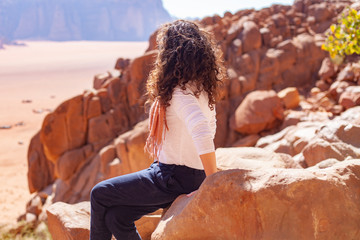 Woman sitting on a rock in a desert