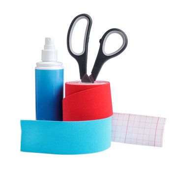 two rolls kinesiology tape for athletes, antibacterial spray and scissors isolated on white background.