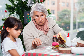 Grandmother teaching her granddaughter how to make christmas Nativity crafts - Real family