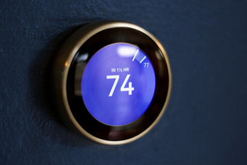 Blue screen round thermostat against a dark blue wall saving money with green tech