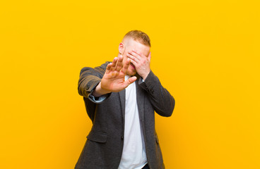 young blond businessman covering face with hand and putting other hand up front to stop camera, refusing photos or pictures