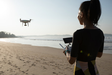 Woman remote control a flying drone which taking photo  on sunrise beach