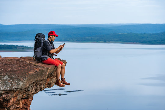 hiker man sitting and using smartphone on edge of cliff, on a top of the rock mountain