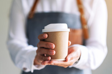 Photo sur Aluminium Cafe A waitress holding and serving a paper cup of hot coffee in cafe