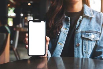 Mockup image of a woman holding and showing black mobile phone with blank screen in cafe