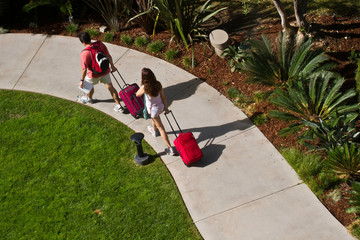 Male and female couple with red roll-on luggage on path viewed from above