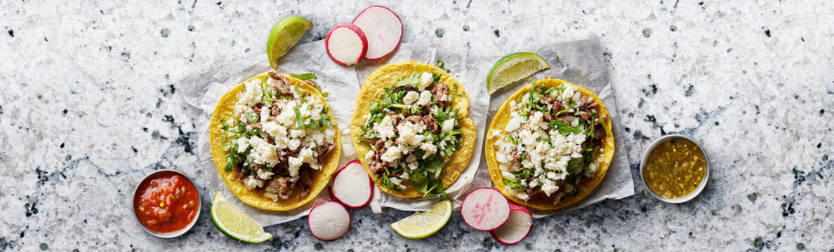 three mexican street tacos with barbacoa and queso fresco cheese in flat lay composition