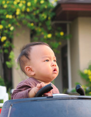 Asian baby boy siting on Toy car
