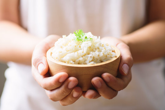 Cooked rice with quinoa seed in bowl holding by hand