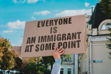 "The phrase "" Everyone is an immigrant at some point "" on a carton banner in men's hand. Human holds a cardboard with an inscription. Government. Power. Immigration. Expats"