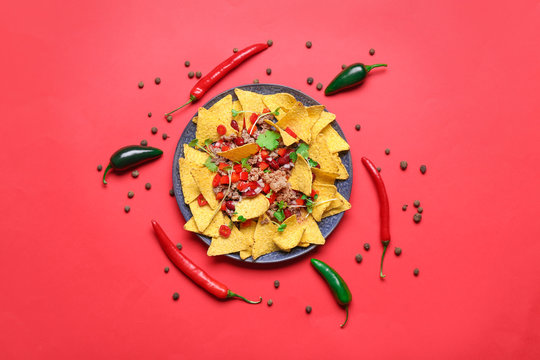 Plate with tasty chili con carne and nachos on color background