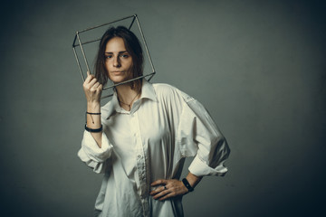 portrait of a girl in a white shirt with a metal cube-cage on his head. isolate. The concept of estrangement, the man in a case