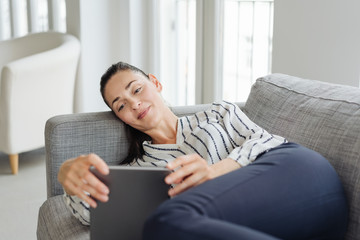 Young woman using tablet while lying on sofa