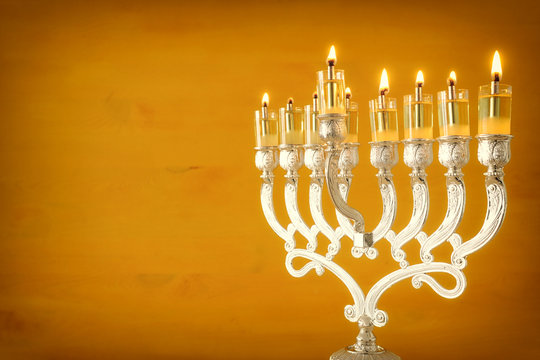 Religion image of jewish holiday Hanukkah background with menorah (traditional candelabra) and oil candles over yellow background