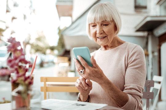 Nice elderly woman looking at her smartphone screen