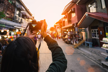Young traveler taking photo with camera in walking street.