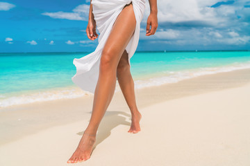 Elegant woman walking on Caribbean beach with slim smooth legs for skin care sun tan wearing cover-up sarong wrap beachwear skirt relaxing on tropical travel holiday.