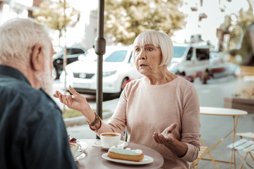 Cheerless aged woman having a quarrel with her husband