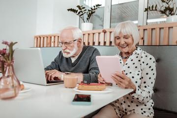 Pleasant elderly people using modern digital devices
