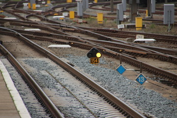 Orange sign light between railroad tracks at Amersfoort station which means speed reduction