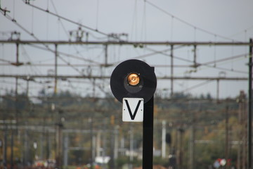 White light sign with letter V on a platform at Amersfoort railroad station. When lit trains may leave the station