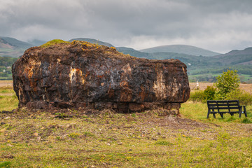 The Plug (remainder of the Ironworks), with a bench next to it and the Lake District in the background, seen at the Millom Ironworks Nature Reserve, Cumbria, England