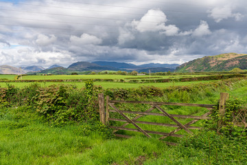 A wooden gate with clouds over the Lake District National Park in the background, seen near Gubbergill, Cumbria, England, UK