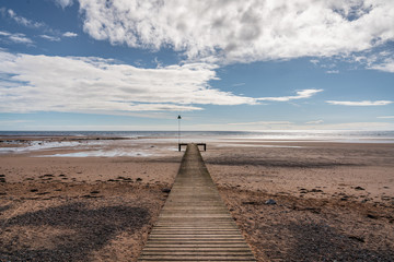 The beach and a wooden walkway in Seascale, Cumbria, England, UK
