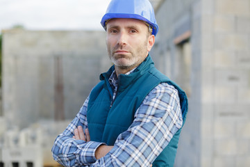 portrait of confident mid adult manual worker with arms crossed