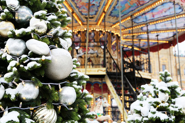Festive carousel and Christmas trees covered by snow. Concept of New Year celebration, winter holidays and entertainment