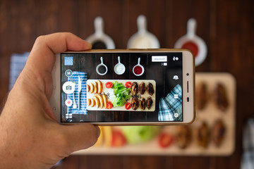 Man taking photo by smart phone from top of the wooden restaurant table with colorful meal