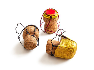 Three used wine champagne corks with a muselet and multi-colored foil