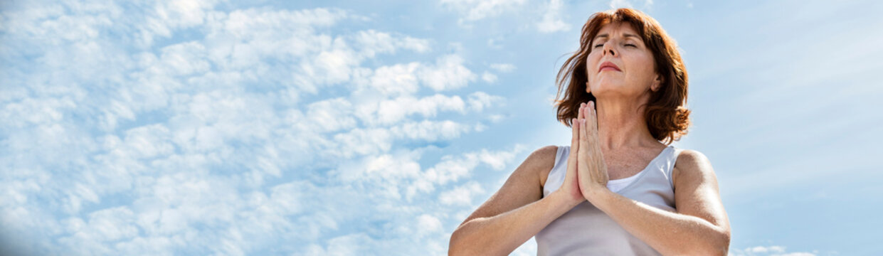 mature woman praying in yoga position with blue sky, banner