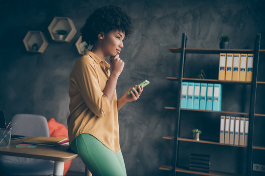 Profile side photo of concentrated afro american girl entrepreneur freelancer use smartphone think thoughts decide choose start-up career solution in office loft