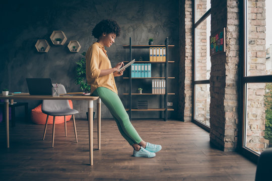 Full size profile side photo of cool smart afro american girl entrepreneur use tablet work read start-up news wear yellow shirt green pants trousers in office loft