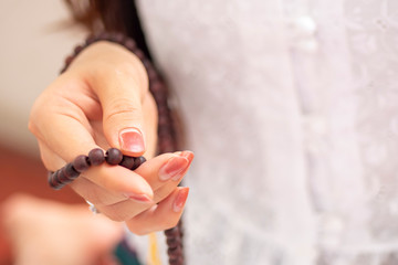 Religious Asian buddhist woman praying with hand holding rosary beads. Female buddhist disciple meditating, chanting mantra with rosary beads prayer in hand to the statue of lord Buddha in temple hall
