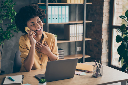 Photo of sincere cheerful mixed-race laughing girl speaking by phone with her friend colleague enjoying her break with pens notepad on desktop
