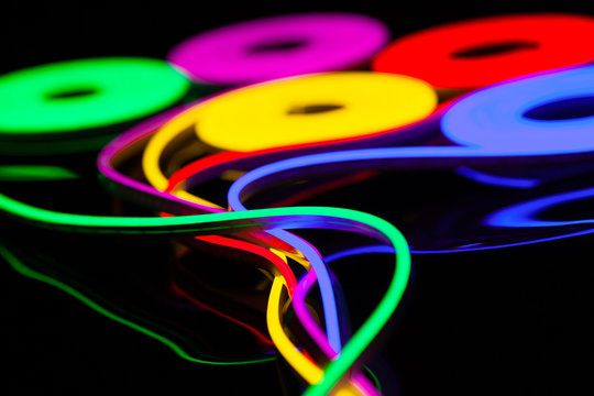 Flexible led tape neon flex in different colors on black background.