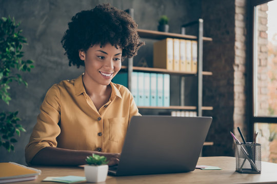 Photo of cheerful positive mixed-race girl smiling toothily working on presentation about her corporation using laptop on desktop