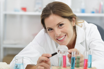 happy woman is looking in a magnifying glass laboratory