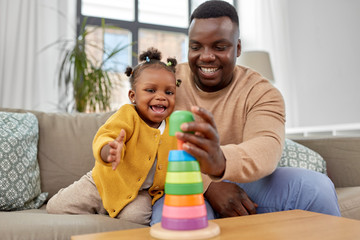 family, parenthood and people concept - happy african american father and baby daughter playing...
